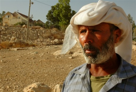 Bedouin stands in front of settlement (photo: IRIN)